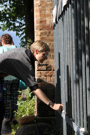 A women putting a candle down in front of a fence