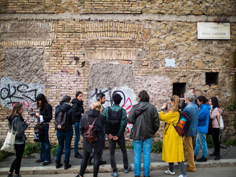 A crowd of people in front of a wall