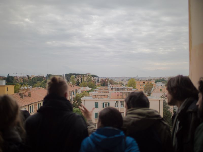 People on roof top, looking over city Rome