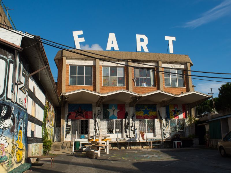 An old factory building, on the roof spelling the word fart in big letters