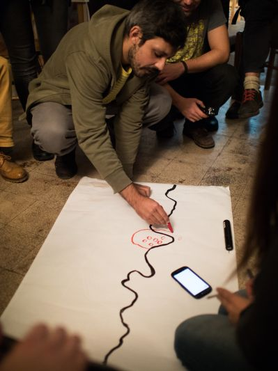 A man drawing on paper on the floor